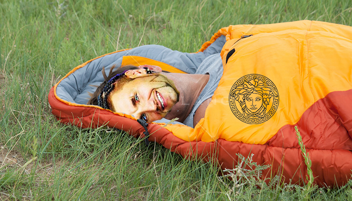 man resting in a sleeping bag on a grassy field